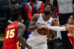 Philadelphia 76ers center Joel Embiid, center, is defended by Atlanta Hawks guard Trae Young (11) and center Clint Capela (15) during the second half of Game 3 of a second-round NBA basketball playoff series Friday, June 11, 2021, in Atlanta. (AP Photo/John Bazemore)