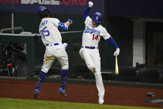 Los Angeles Dodgers' Cody Bellinger celebrates his home run with Enrique Hernandez against the Atlanta Braves during the seventh inning in Game 7 of a baseball National League Championship Series Sunday, Oct. 18, 2020, in Arlington, Texas.(AP Photo/Tony Gutierrez)