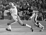 File-This Jan. 18, 1976, file photo shows Pittsburgh Steeler Dwight White (78), chasing down Dallas Cowboys quarterback Roger Staubach in the second quarter of Super Bowl X in Miami.  Members of a special panel of 26 selected all of them for the position as part of the NFL's celebration of its 100th season. All won league titles except Marino. All are in the Hall of Fame except Brady and Manning, who are not yet eligible.  On Friday night, quarterback was the final position revealed for the All-Time Team.  (AP Photo/File)