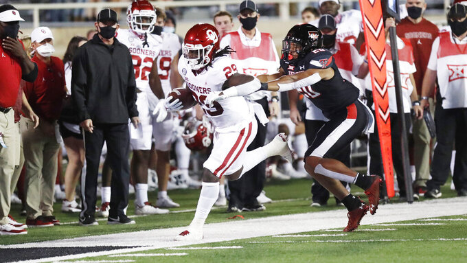 Oklahoma running back Rhamondre Stevenson steps out of bounds under pressure from Texas Tech linebacker Kosi Eldridge during the first half of an NCAA college football game Saturday, Oct. 31, 2020, in Lubbock, Texas.(AP Photo/Mark Rogers)