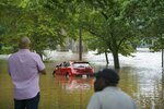 Bystanders observe a vehicle and driver stuck in flood water on Kelly Drive at Midvale Ave.,  on Friday, July 12, 2019 in Philadelphia. A series of storms socked the Northeast with heavy rains and strong winds.  (Jessica Griffin/The Philadelphia Inquirer via AP)
