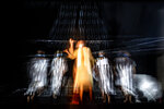 In this photograph shot with a slow shutter speed Romanian Jewish actress Maia Morgernstern, center, performs alongside fellow actresses of the Jewish State Theatre, wearing face masks for protection against  COVID-19 infection, during rehearsals for the premiere of the