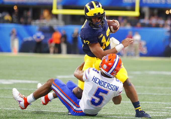 Michigan running back Chris Evans (12) runs into Florida defensive back CJ Henderson (5) during the first half of the Peach Bowl NCAA college football game, Saturday, Dec. 29, 2018, in Atlanta. (AP Photo/John Bazemore)