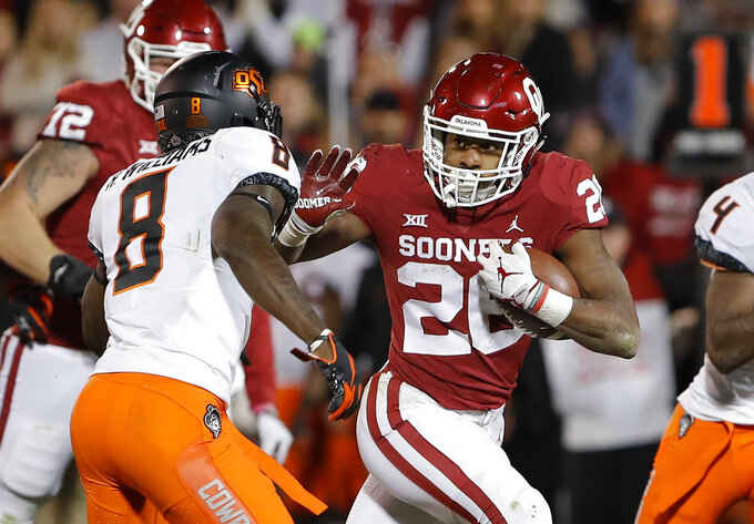 Oklahoma running back Kennedy Brooks (26) runs as Oklahoma State cornerback Rodarius Williams (8) comes in for the tackle in the second half of an NCAA college football game in Norman, Okla., Saturday, Nov. 10, 2018. Oklahoma won 48-47. (AP Photo/Alonzo Adams)