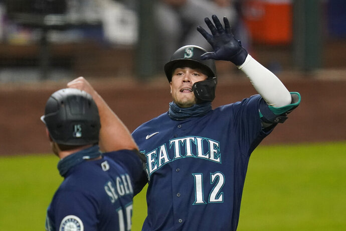 Seattle Mariners' Evan White (12) is congratulated by Kyle Seager after hitting a three-run home run against the Houston Astros in the seventh inning of a baseball game Monday, Sept. 21, 2020, in Seattle. (AP Photo/Elaine Thompson)