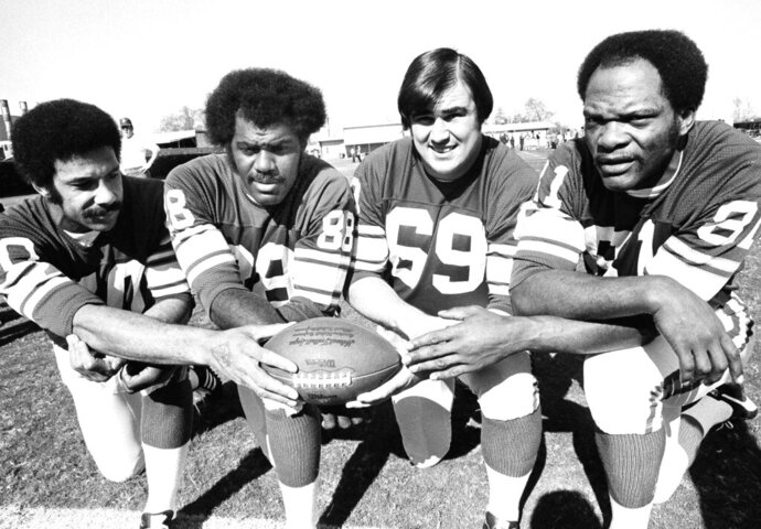 "FILE - This Jan. 9, 1975, file photo shows from left, Minnesota Vikings defensemen  Jim Marshall, Alan Page, Doug Sutherland and Carl Eller. ""Purple People Eaters"" _ The bruising Minnesota Vikings defensive line from the late 1960s through the 1970s. Members included Hall of Famer Alan Page, Carl Eller and Jim Marshall. If not for going 0-4 in Super Bowls, the group likely would be more celebrated. (AP Photo/File)"