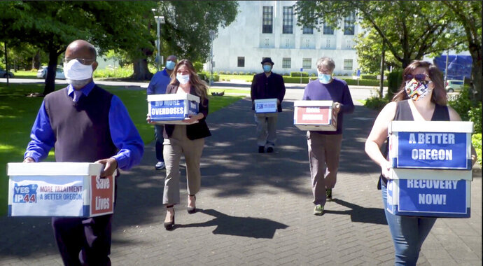 This photo from video provided by the Yes on Measure 110 Campaign shows volunteers delivering boxes containing signed petitions in favor of the measure to the Oregon Secretary of State's office in Salem on June 26, 2020. In what would be a first in the U.S., possession of small amounts of heroin, cocaine, LSD and other hard drugs could be decriminalized in Oregon under a ballot measure that voters are deciding on in Tuesday's election. Oregon's Measure 110 is one of the most watched referendums in the state because it would drastically change how the justice system treats people with amounts of the drugs for their personal use. Instead of going to trial and facing possible jail time, people caught with the drugs would have the option of paying $100 fines or attending new