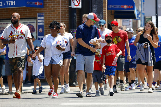 People cross a street as they make their way towards Chicago's Wrigley Field during baseball game, Friday, June 11, 2021, as Chicago and rest of Illinois fully reopens ending an over a year-long COVID-19 restrictions. (AP Photo/Shafkat Anowar)