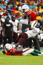 Miami wide receiver Mike Harley (3) leaps over Bethune-Cookman cornerback Henry Miller II as he runs for yardage during the second half of an NCAA college football game, Saturday, Sept. 14, 2019, in Miami Gardens, Fla. (AP Photo/Wilfredo Lee)