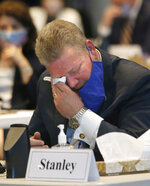 State Sen. Bill Stanley, R-Franklin, wipes a tear during the eulogy of his friend, the late Sen. Ben Chafin, R-Russell, as members of the Virginia Senate convene for opening day of the General Assembly inside the Science Museum in Richmond, Va., Wednesday, Jan. 13, 2021. Chafin died on Jan. 1 due to complications related to the coronavirus. (Bob Brown/Richmond Times-Dispatch via AP)