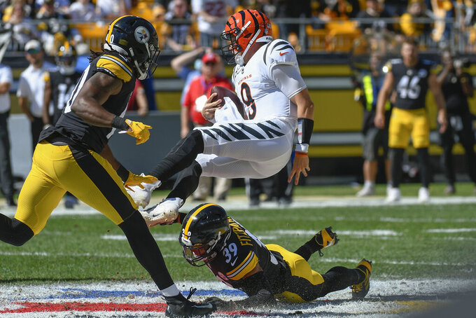 Cincinnati Bengals quarterback Joe Burrow (9) tumbles over Pittsburgh Steelers free safety Minkah Fitzpatrick (39) as linebacker Jamir Jones (40) pursues during the first half an NFL football game, Sunday, Sept. 26, 2021, in Pittsburgh. (AP Photo/Don Wright)