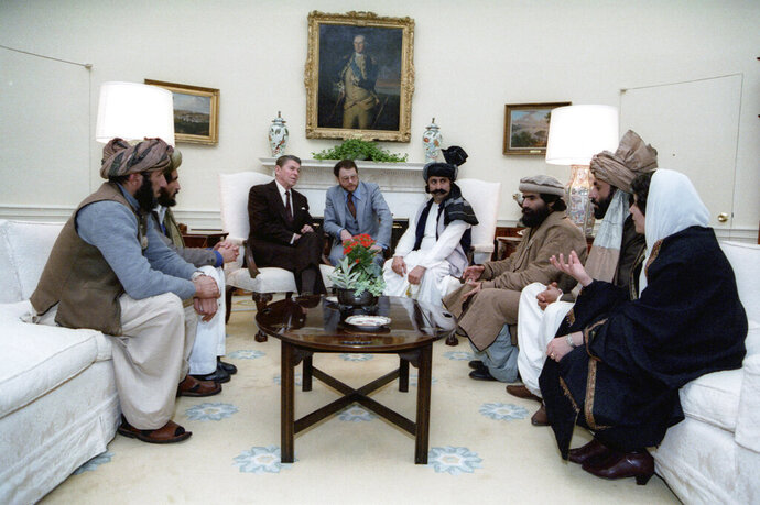 UPDATES INFORMATION - In this photo courtesy Ronald Reagan Library, then President Ronald Reagan meets with Afghan