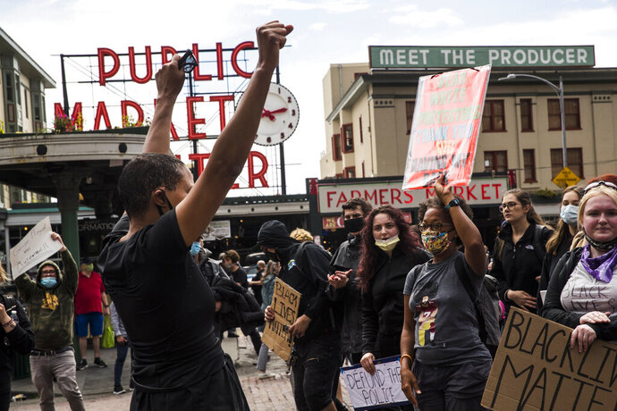 Protesters continue past Pike Place Market during the #SeattleJusticeForGeorgeFloyd march on Saturday, June 6, 2020, in Seattle, Washington. The death of George Floyd at the hands of police last month in Minneapolis has sparked nationwide protests for police reform. (Amanda Snyder/The Seattle Times via AP)