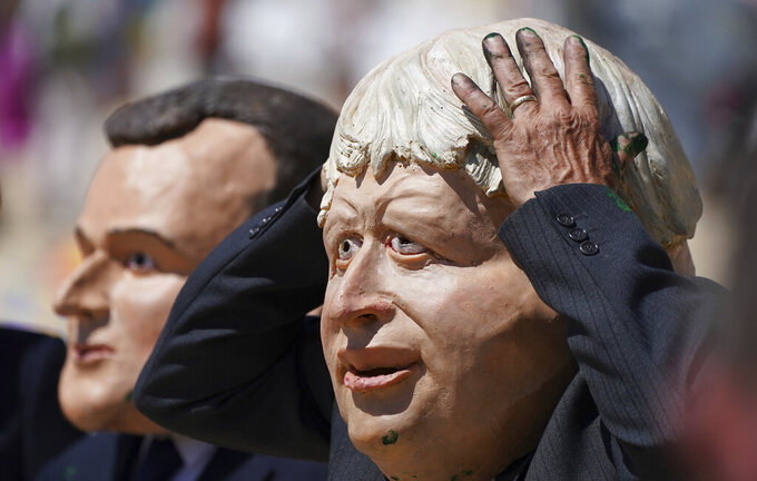 Protestors wearing giant heads portraying G7 leaders British Prime Minister Boris Johnson, right, and French President Emmanuel Macron participate in a demonstration on a beach outside the G7 meeting in St. Ives, Cornwall, England, Sunday, June 13, 2021. Leaders of the G7 wrap up three days of meetings in Carbis Bay Sunday, in which they discussed such topics as COVID-19, climate, foreign policy and the economy. (AP Photo/Jon Super)