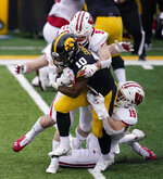 Iowa running back Mekhi Sargent (10) is tackled by Wisconsin safety Scott Nelson (9) and linebacker Nick Herbig (19) during the first half of an NCAA college football game, Saturday, Dec. 12, 2020, in Iowa City, Iowa. (AP Photo/Charlie Neibergall)