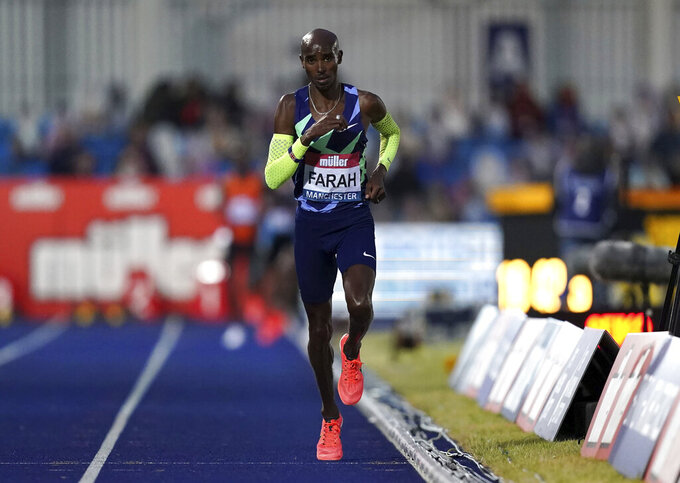 Britain's Mo Farah competes in the Men's 10000m final during day one of the British Athletics Championships at Manchester Regional Arena in England, Friday June 25, 2021. Mo Farah failed to qualify for the Tokyo Olympics and will not defend his 10,000-meter title. The four-time Olympic champion missed the qualifying time in an invitational 10,000 at the British athletics championships in Manchester.  (Martin Rickett/PA via AP)