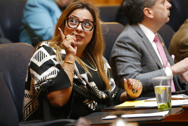 Del. Elizabeth Guzman, R-Fairfax, speaks to a fellow legislator after a vote on a collective bargaining bill during the House session at the Capitol Sunday March 8, 2020, in Richmond, Va. (AP Photo/Steve Helber)