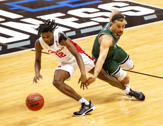 Cleveland State guard Tre Gomillion (5), right, tries to steal the ball away from Houston guard Tramon Mark (12) during the second half of a first-round game in the NCAA men's college basketball tournament, Friday, March 19, 2021, at Assembly Hall in Bloomington, Ind. (AP Photo/Doug McSchooler)