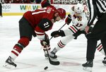 Arizona Coyotes center Derek Stepan (21) beats Chicago Blackhawks center Dylan Strome (17) to the puck on a face off during the first period of an NHL hockey game Tuesday, March 26, 2019, in Glendale, Ariz. (AP Photo/Ross D. Franklin)
