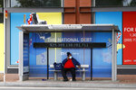 A man sits at a bus stop while wearing a face mask Thursday, May 21, 2020, in Washington. The District of Columbia is under a stay-home order for all residents in an effort to slow the spread of the new coronavirus. (AP Photo/Patrick Semansky)