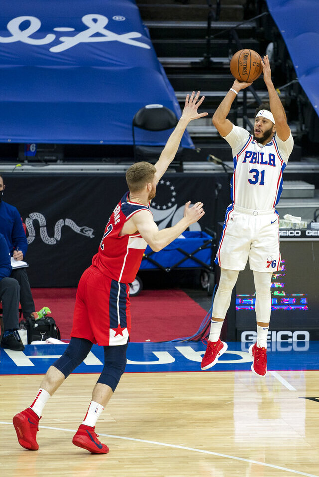 Philadelphia 76ers guard Seth Curry, right, shoots a three-pointer over Washington Wizards forward Davis Bertans, left, during the first half of an NBA basketball game, Wednesday, Jan. 6, 2021, in Philadelphia. (AP Photo/Chris Szagola)