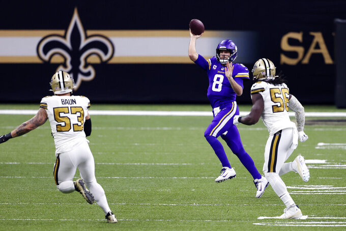 Minnesota Vikings quarterback Kirk Cousins (8) passes as he is pursued by New Orleans Saints outside linebacker Demario Davis (56) and linebacker Zack Baun (53) in the first half of an NFL football game in New Orleans, Friday, Dec. 25, 2020. (AP Photo/Butch Dill)