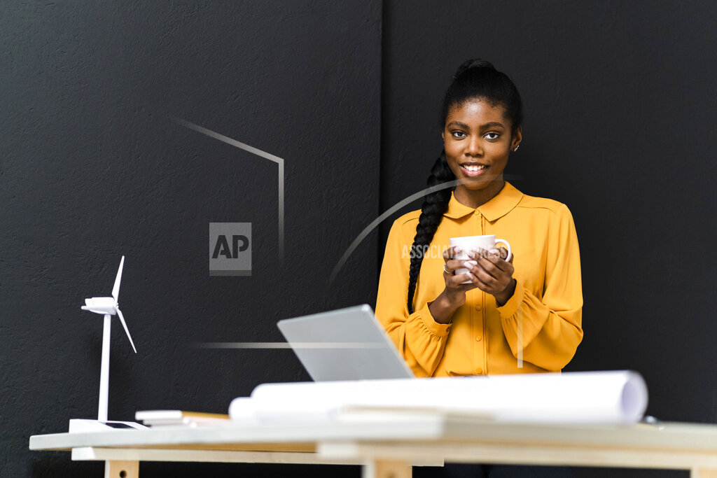 Businesswoman holding coffee mug in front of black wall while working at studio