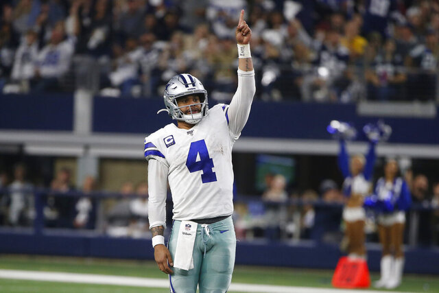 FILE-Dallas Cowboys quarterback Dak Prescott (4) celebrates a touchdown against the Washington Redskins during the second half of an NFL football game in Arlington, Texas, Sunday, Dec. 15, 2019.  Prescott stuck with his virtual hiatus trying to get a long-term contract that never came during the offseason. Now that the star quarterback of the Dallas Cowboys is in the building preparing to play on the $31.4 million franchise tag, Prescott doesn't see an immediate need for questions about his future with America's Team. (AP Photo/Ron Jenkins, File)