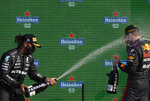 Second placed Mercedes driver Lewis Hamilton of Britain, left, sprays champagne on a race winner Red Bull driver Max Verstappen of the Netherlands after the Formula One Dutch Grand Prix, at the Zandvoort racetrack, Netherlands, Sunday, Sept. 5, 2021. (AP Photo/Peter Dejong)