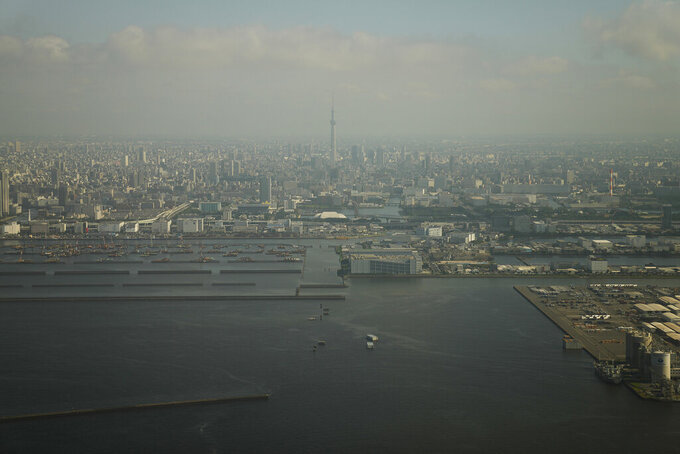 The Tokyo Skytree is seen through the window of an airplane upon approaching Haneda Airport in Tokyo, Monday, July 19, 2021. (AP Photo/Natacha Pisarenko)