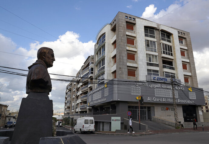 A statue of Iranian General Qassem Soleimani, former head of Iran's Quds force, stands in front of a branch of the Hezbollah-run Qard al-Hassan Association, in Ghobeiry, Lebanon, Wednesday, Jan. 20, 2021. As more Lebanese fall into poverty in the country's economic crisis, increasing numbers are turning to the financial arm of the Iranian-backed Hezbollah militant group for help. Qard al-Hassan provides small, interest-free loans in dollars at a time when Lebanese are desperate for hard currency and commercial banks are not lending. (AP Photo/Bilal Hussein)