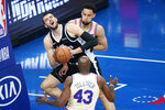 Los Angeles Clippers' Ivica Zubac center, tries to pass between Philadelphia 76ers' Ben Simmons, top, and Anthony Tolliver during the second half of an NBA basketball game, Friday, April 16, 2021, in Philadelphia. (AP Photo/Matt Slocum)
