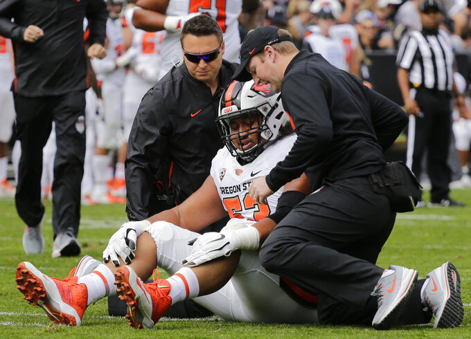 Oregon State offensive lineman Gus Lavaka is tended to by trainers after sustaining an injury during the first half of an NCAA college football game against Colorado, Saturday, Oct. 27, 2018, in Boulder, Colo. (AP Photo/Jack Dempsey)