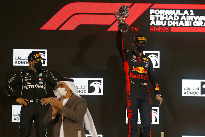 Red Bull driver Max Verstappen of the Netherlands celebrates wining as Mercedes driver Valtteri Bottas of Finland ,left, looks on after the Formula One at the Yas Marina racetrack in Abu Dhabi, United Arab Emirates, Sunday, Dec.13, 2020. (Hamad Mohammed, Pool via AP)