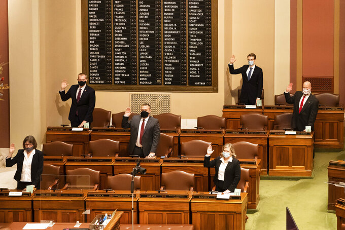 FILE - In this Jan. 5, 2021, file photo, a few legislators are sworn-in in person at the House Chamber and most were sworn in remotely in groups of nine at a time, via Zoom at the Minnesota State Capitol, in St. Paul, Minn. As the Minnesota Legislature enters the last full week of its 2021 session, lawmakers face long hours of tough negotiations as they seek to agree on a balanced budget by the Monday, May 10, 2021, mandatory adjournment date. (Glen Stubbe/Star Tribune via AP, File)