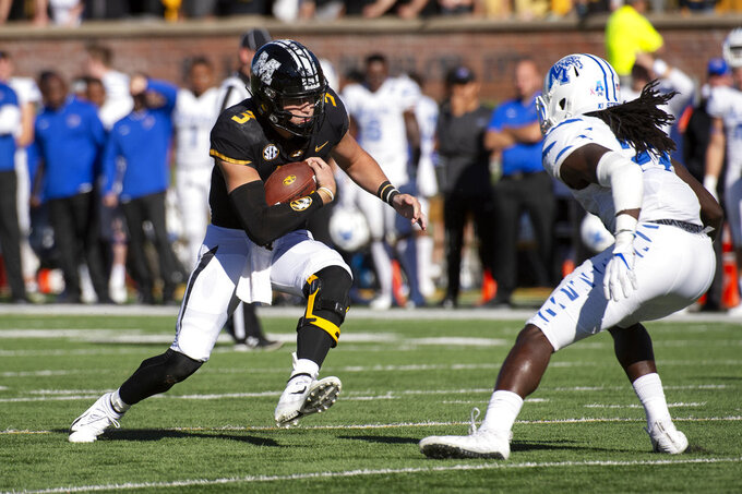 Missouri quarterback Drew Lock runs the ball as Memphis' JJ Russell, right, prepares to tackle him during the first half of an NCAA college football game, Saturday, Oct. 20, 2018, in Columbia, Mo. Missouri won the game 65-33. (AP Photo/L.G. Patterson)