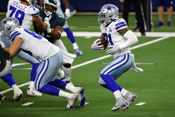 Dallas Cowboys running back Ezekiel Elliott (21) runs the ball in the second half of an NFL football game against the Philadelphia Eagles in Arlington, Texas, Sunday, Dec. 27. 2020. (AP Photo/Michael Ainsworth)