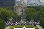 Un grupo de visitantes guardan un minuto de silencio en honor de las víctimas de la bomba atómica que cayó sobre Hiroshima en conmemoración del 75to aniversario de ese ataque, el jueves 6 de agosto de 2020, en Hiroshima, Japón. Al fondo se ve el Memorial de la Paz, las ruinas del único edificio que quedó en pie. (AP Foto/Eugene Hoshiko)