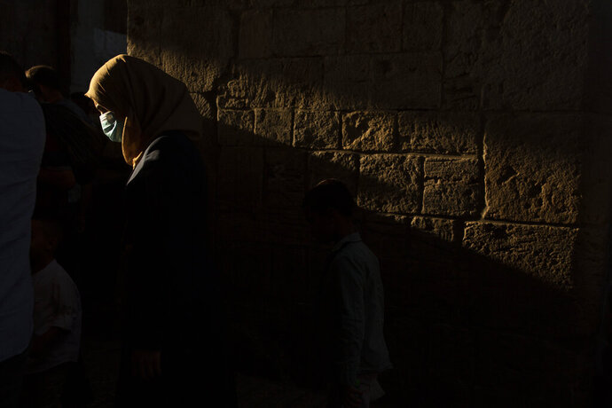 A woman wears a mask to help curb the spread of the coronavirus as she leaves prayers for Eid Al-Adha, or feast of sacrifice, in the Old City of Jerusalem, Friday, July 31, 2020. A key holiday on the Muslim calendar, Eid Al-Adha celebrations are somewhat subdued this year due to the coronavirus and the measures in place to curb its spread. (AP Photo/Maya Alleruzzo)