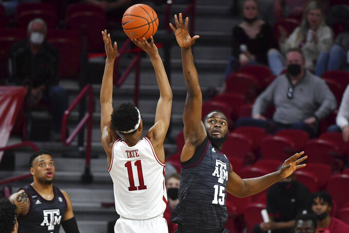 Texas A&M forward Jonathan Aku (15) puts pressure on Arkansas guard Jalen Tate (11) who shoots during the second half of an NCAA college basketball game in Fayetteville, Ark., Saturday, March 6, 2021. (AP Photo/Michael Woods)
