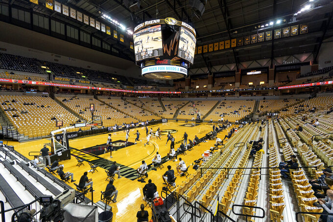 A sparse crowd, owing to COVID-19 restrictions, watches the first half of an NCAA college basketball game between Missouri and Oral Roberts on Wednesday, Nov. 25, 2020, in Columbia, Mo. (AP Photo/L.G. Patterson)
