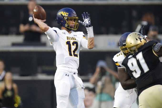 Northern Colorado quarterback Dylan McCaffrey, left, passes the ball as Colorado defensive lineman Na'im Rodman pursues in the first half of an NCAA college football game Friday, Sept. 3, 2021, in Boulder, Colo. (AP Photo/David Zalubowski)