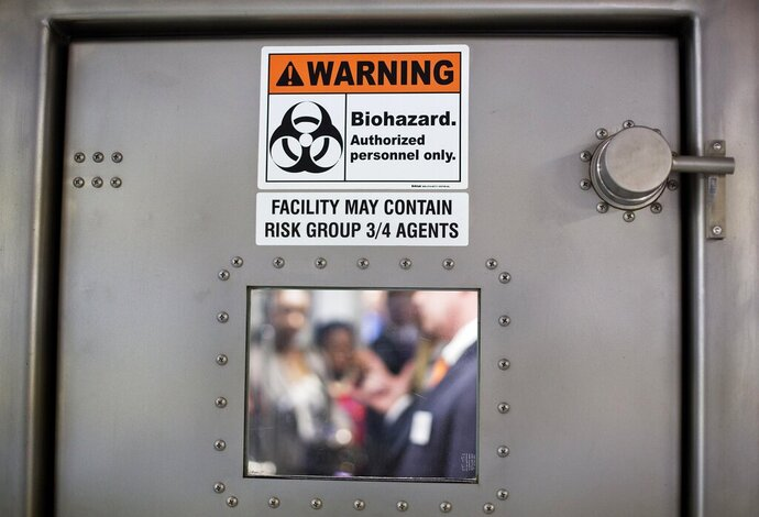 FILE-In this Tuesday, Aug. 11, 2015 file photo, a warning sign is posted to the door of a medevac biocontainment unit aboard a military transport plane at Dobbins Air Force Reserve Base during a media tour, in Marietta, Ga. Some of the first Ebola virus patients to be successfully treated in the United States are reuniting five years later with the medical team that treated them at Emory University Hospital in Atlanta. (AP Photo/David Goldman, File)