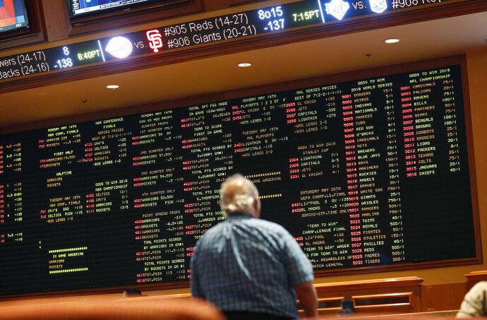 In this Monday, May 14, 2018 photo, betting odds are displayed on a board in the sports book at the South Point hotel and casino in Las Vegas. Now that the U.S. Supreme Court has cleared the way for states to legalize sports betting, the race is on to see who will referee the multi-billion-dollar business expected to emerge from the decision. (AP Photo/John Locher)