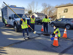 In this photo provided by the University of Nevada, Reno, a research crew poses next to a manhole in Sparks, Nev., in December 2020, where they took samples for a study comparing wastewater concentrations of the virus that causes COVID-19 and trends in coronavirus cases in the community. Scientists say data sampled from sewers and wastewater treatment plants in the Reno-Sparks area last year showed a correlation to the number of positive tests for coronavirus that would follow in about seven days. (Laura Haak/University of Nevada, Reno via AP)