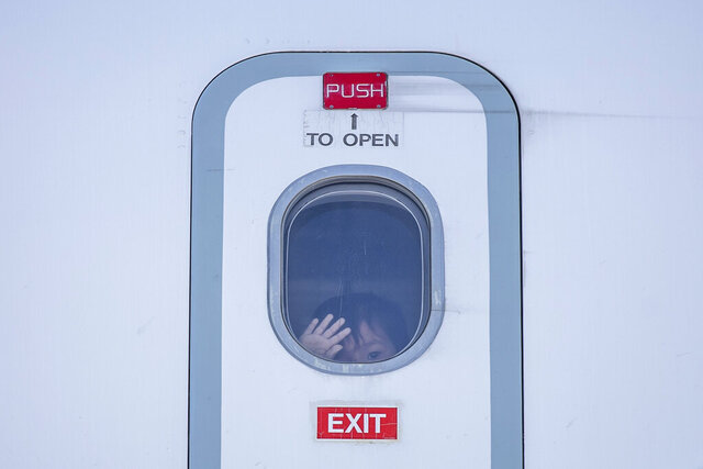 A child looks out of a window of a plane as a group of migrant children with health issues board a plane to Germany, at Athens International Airport, Friday, July 24, 2020. German Foreign Heiko Maas, on a visit to Athens this week, said his country would follow through in its pledge to assist Greece with the relocation of unaccompanied minors and other children at refugee camps in Greece. (AP Photo/Petros Giannakouris)