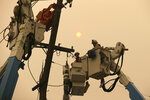 FILE - In this Nov. 9, 2018 file photo, Pacific Gas & Electric crews work to restore power lines in Paradise, Calif. Pacific, Gas & Electric Co. initially planned to de-energize local powers lines in vulnerable rural areas during high winds, but has expanded its precautionary power outages to urban areas that could mean multi-day blackouts for cities as larges as San Francisco and San Jose, which could endanger some who depend on electricity for their life support. (AP Photo/Rich Pedroncelli, File)