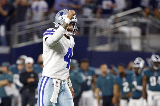 Dallas Cowboys' Dak Prescott (4) celebrates a touchdown scored on a run by running back Ezekiel Elliott (21) in the first half of an NFL football game against the Philadelphia Eagles in Arlington, Texas, Monday, Sept. 27, 2021. (AP Photo/Ron Jenkins)