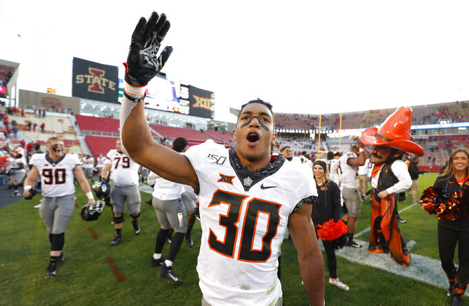 FILE - In this Oct. 26, 2019, file photo, Oklahoma State running back Chuba Hubbard blows a kiss to Oklahoma State fans after their 34-27 win over Iowa State in an NCAA college football game in Ames, Iowa. After the Power Five conference commissioners met Sunday, Aug. 9, 2020, to discuss mounting concern about whether a college football season can be played in a pandemic, players took to social media to urge leaders to let them play. (AP Photo/Matthew Putney, File)
