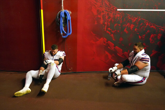 Buffalo Bills guard Ike Boettger, right, and offensive tackle Spencer Brown, left, sit in a tunnel off the field as they wait for the start of the second half during a weather delay at halftime of an NFL football game Sunday, Oct. 10, 2021, in Kansas City, Mo. (AP Photo/Charlie Riedel)